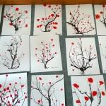Consigne: créer des arbustes et branches en souflant avec une paille sur l'encre de chine. Peindre des fleurs de différentes tailles, positionnées de façon différentes sur les branches.